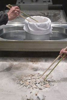 After cremation bone fragments are transferred by family members into an urn.